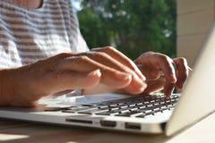 Mulher que usa um laptop, close-up das mãos imagens de stock