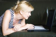 Mulher que usa um portátil foto de stock