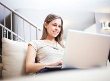 Mulher que usa um portátil imagens de stock