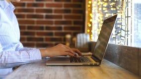 Mulher que usa um portátil durante uma ruptura de café, mãos perto acima vídeos de arquivo