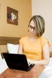 a mulher que usa um portátil relaxou em sua cama Fotos de Stock Royalty Free