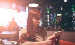 Mulher que usa um telefone celular no restaurante, café, barra foto de stock royalty free