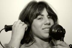Mulher que usa um telefone do vintage foto de stock royalty free