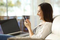 Mulher que usa um telefone e um portátil em casa Fotos de Stock