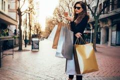 Mulher que usa um telefone esperto ao comprar na cidade Foto de Stock