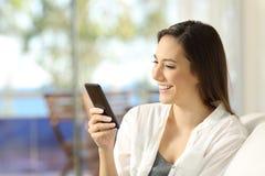 Mulher que usa um telefone esperto em um apartamento Imagem de Stock Royalty Free