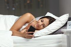 Mulher que usa um telefone esperto na noite em uma cama em casa fotografia de stock royalty free
