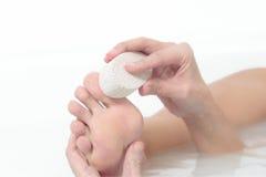 Mulher que usa uma pedra de polimento para exfoliate seus pés Foto de Stock