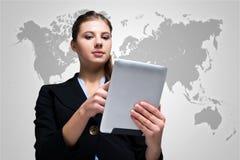 Mulher que usa uma tabuleta digital na frente de um mapa do mundo fotos de stock
