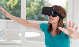 Mulher que usa uns auriculares da realidade virtual fotografia de stock