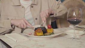 A mulher que vai comer belamente serviu a carne do apetite ou a carne do cordeiro com milho e abobrinha do assado Fim acima vídeos de arquivo