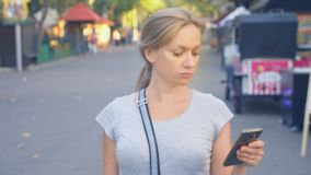 Mulher que vai estacionar com seu telefone no dia de verão sob a luz do sol 4k, lento-movimento, tiro do standicam video estoque