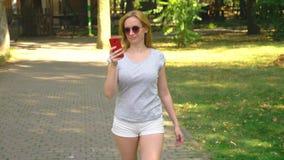 Mulher que vai estacionar com seu telefone no dia de verão sob a luz do sol 4k, lento-movimento, tiro do standicam vídeos de arquivo