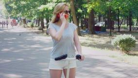 Mulher que vai estacionar com seu telefone no dia de verão sob a luz do sol 4k, lento-movimento, tiro do standicam filme
