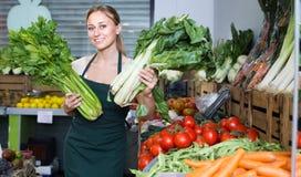 Mulher que vende verdes frescos no mercado Imagem de Stock Royalty Free