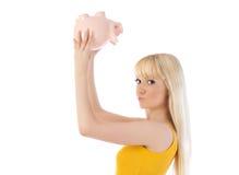 Mulher que verific o banco piggy para ver se há o dinheiro Imagens de Stock