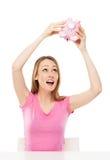 Mulher que verific o banco piggy para ver se há o dinheiro Imagens de Stock Royalty Free