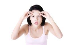 Mulher que verific seus enrugamentos em sua testa Fotografia de Stock Royalty Free