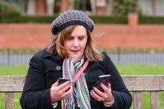 Mulher que verifica dois telefones celulares Fotos de Stock Royalty Free