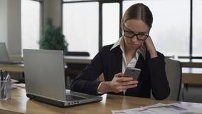 Mulher que verifica meios sociais no telefone, confundido do trabalho, conceito da produtividade filme