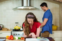 Mulher que verifica o livro e o homem da receita que cozinham no fogão Imagem de Stock
