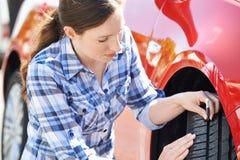 Mulher que verifica o passo no pneumático do carro com o calibre imagens de stock