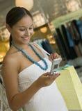 Mulher que verifica o telemóvel ao comprar na loja de roupa Fotos de Stock Royalty Free