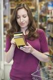 Mulher que verifica a rotulagem na caixa no supermercado fotos de stock royalty free
