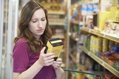 Mulher que verifica a rotulagem na caixa no supermercado foto de stock royalty free