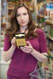 Mulher que verifica a rotulagem na caixa no supermercado imagem de stock royalty free