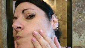 Mulher que verifica sua cara no banheiro video estoque