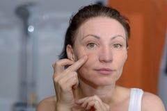 Mulher que verifica sua pele para ver se há sinais do envelhecimento imagens de stock royalty free