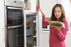 Mulher que verifica a venda na data no saco da salada no refrigerador foto de stock royalty free