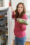 Mulher que verifica a venda na data no saco da salada no refrigerador imagem de stock