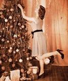 Mulher que veste a árvore de Natal. Foto de Stock