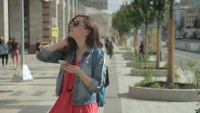 A mulher que veste óculos de sol com telefone está andando em torno da cidade video estoque