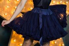 Mulher que veste as meias azuis da saia e da malha do tutu do laço que levantam o ov Foto de Stock Royalty Free