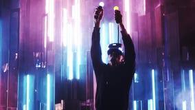 Mulher que veste auriculares de VR e as mãos moventes na luz de néon vídeos de arquivo