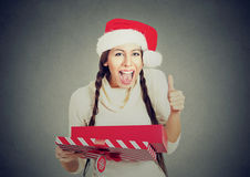 Mulher que veste a caixa de presente da abertura do chapéu de Papai Noel que mostra os polegares acima Fotos de Stock