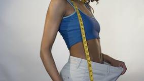 A mulher que veste calças fracas, mostrando a perda de peso resulta, mantendo a maçã disponivel vídeos de arquivo