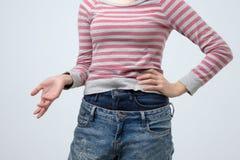 Mulher que veste duas calças das calças de brim Forma estranha e impar É muito superficial fotos de stock