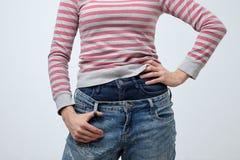 Mulher que veste duas calças das calças de brim Forma estranha e impar É muito superficial imagens de stock