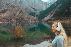 Mulher que veste fones de ouvido sem fio no lago imagem de stock