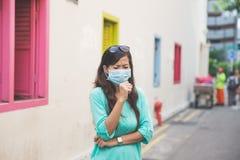 Mulher que veste a máscara protetora médica na cidade imagens de stock royalty free