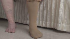 Mulher que veste meias médicas contra as veias varicosas nos pés, tratamento vídeos de arquivo