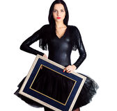Mulher que veste no vestido preto que guarda a moldura para retrato Foto de Stock Royalty Free