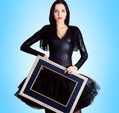 Mulher que veste no vestido preto que guarda a moldura para retrato fotos de stock