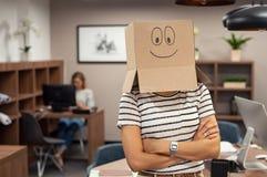 Mulher que veste o cartão feliz da cara no escritório foto de stock royalty free