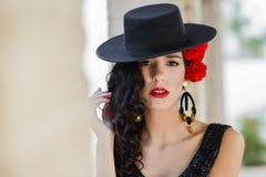 Mulher que veste o chapéu espanhol e cravos vermelhos em seu cabelo fotografia de stock