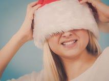 Mulher que veste o chap?u de Santa que cobre seus olhos imagem de stock royalty free